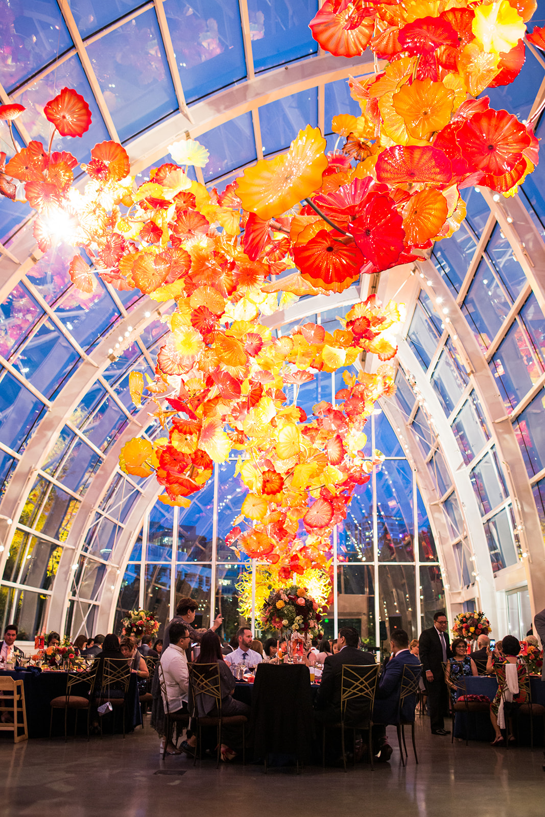 Burnt orange and navy blue evening at a fall wedding reception in the Chilhuly glass house
