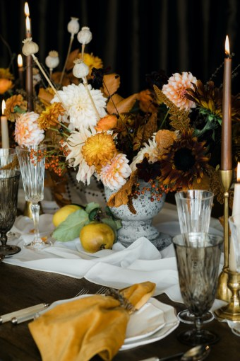 Floral centerpiece for Thanksgiving with orange and peach dahlias, dried poppy pods in stone vase with quince fruit and brown taper candles - Decorating for the Holidays - FLORA NOVA DESIGN SEATTLE