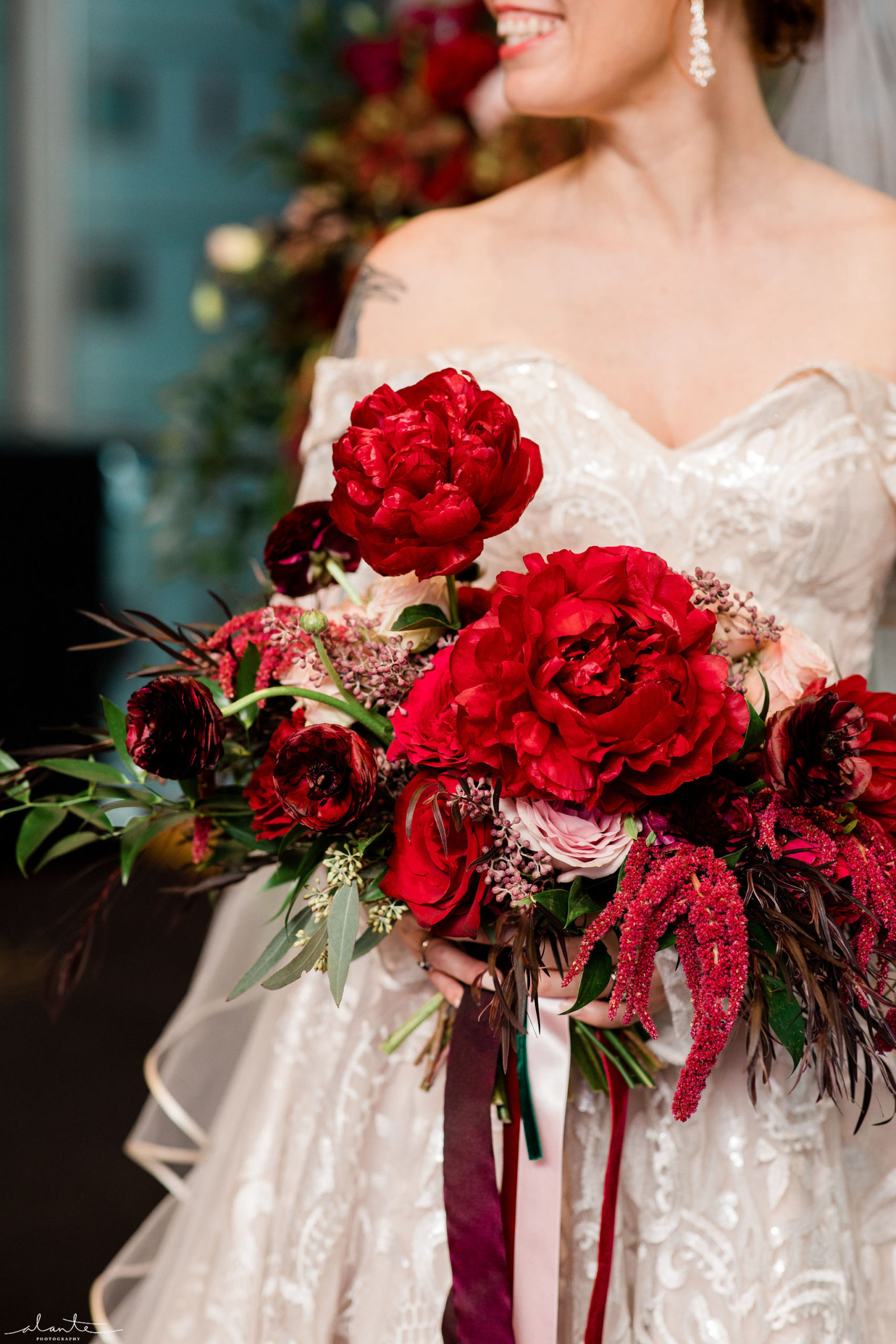 Red peonies, burgundy ranunculus, and seeded eucalyptus are just a few flowers that make up this striking winter bridal bouquet by Flora Nova Design Seattle