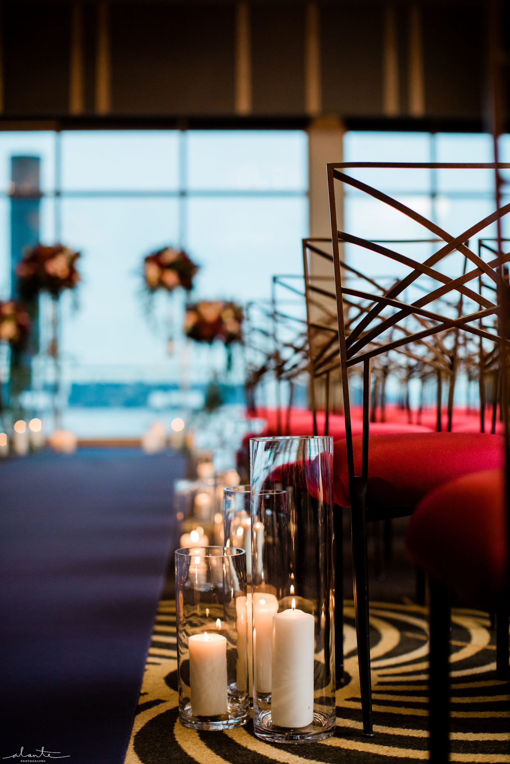 Hurricane candles and gold chameleon chairs with red cushions line the aisle for our red winter wedding ceremony.