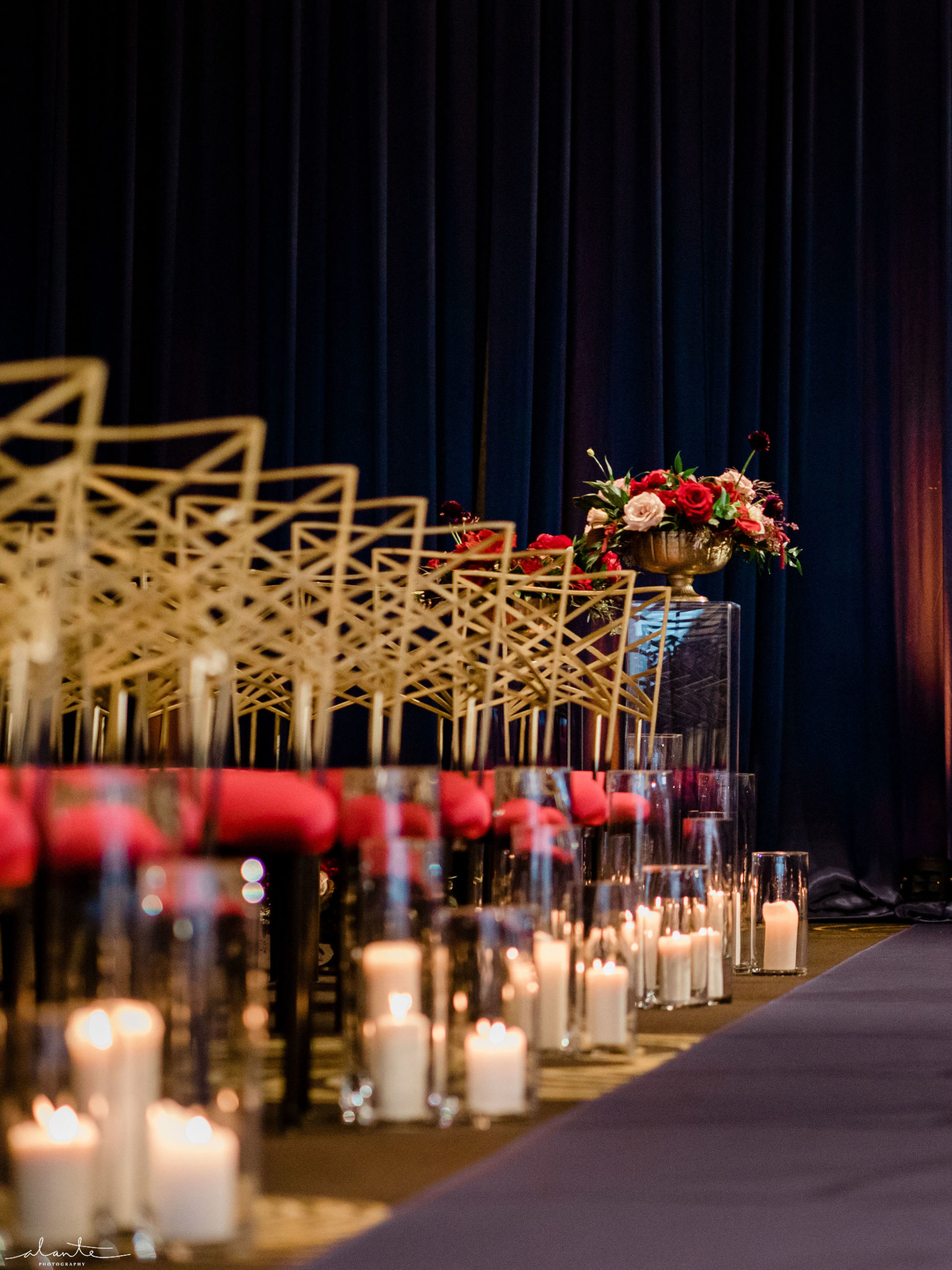 Navy blue aisle runner lined with gold chameleon chairs and hurricane candles paired with red and blush floral for a winter wedding ceremony.