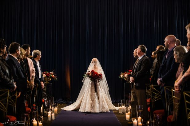 Bride with a red bouquet and full length veil makes a dramatic entrance to her winter ceremony lit by lots of candles lining the aisle | Flora Nova Design Seattle