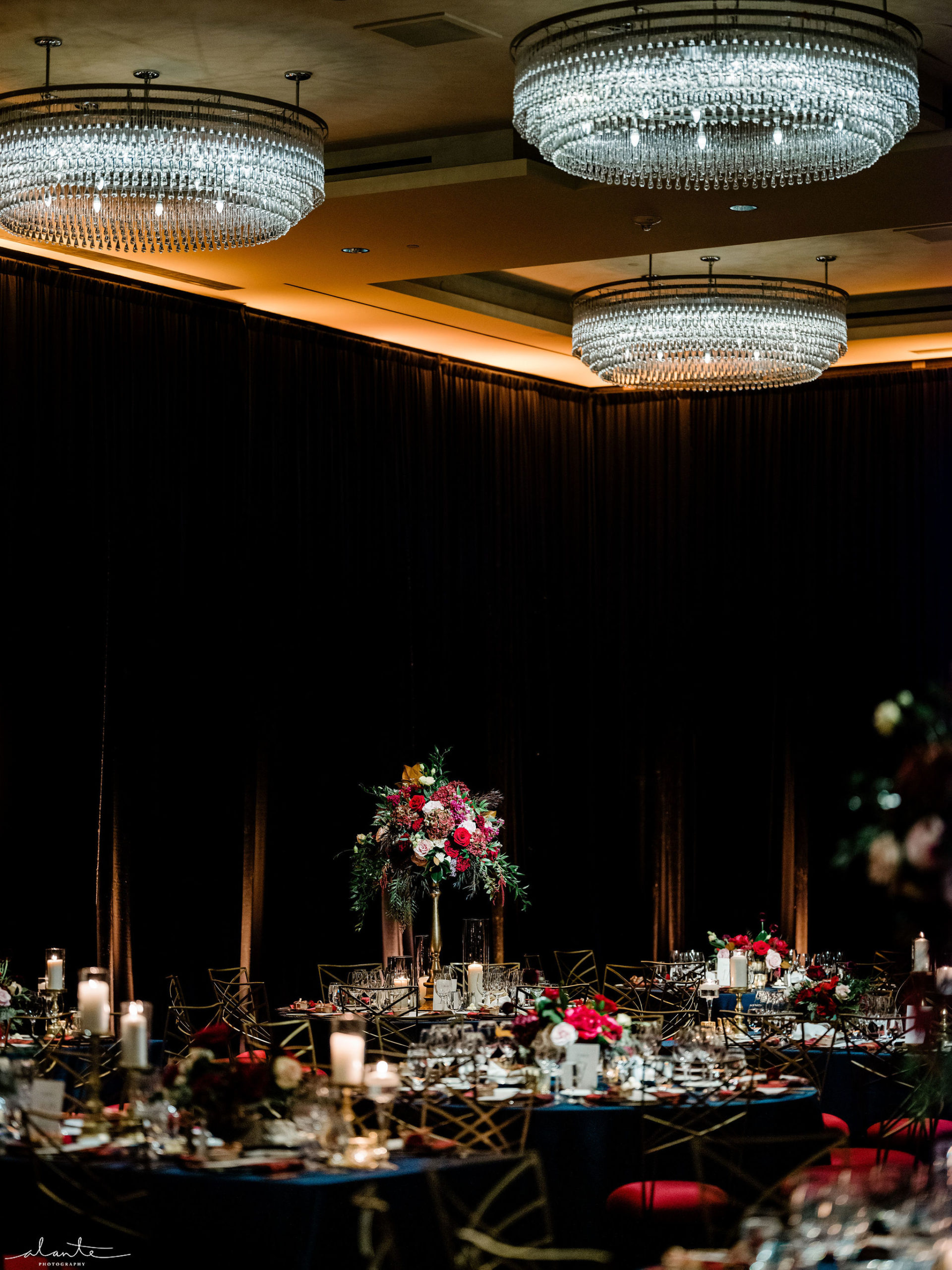 Dramatic December wedding at the Four Seasons Seattle ballroom with tall red floral centerpieces designed by Flora Nova Design.