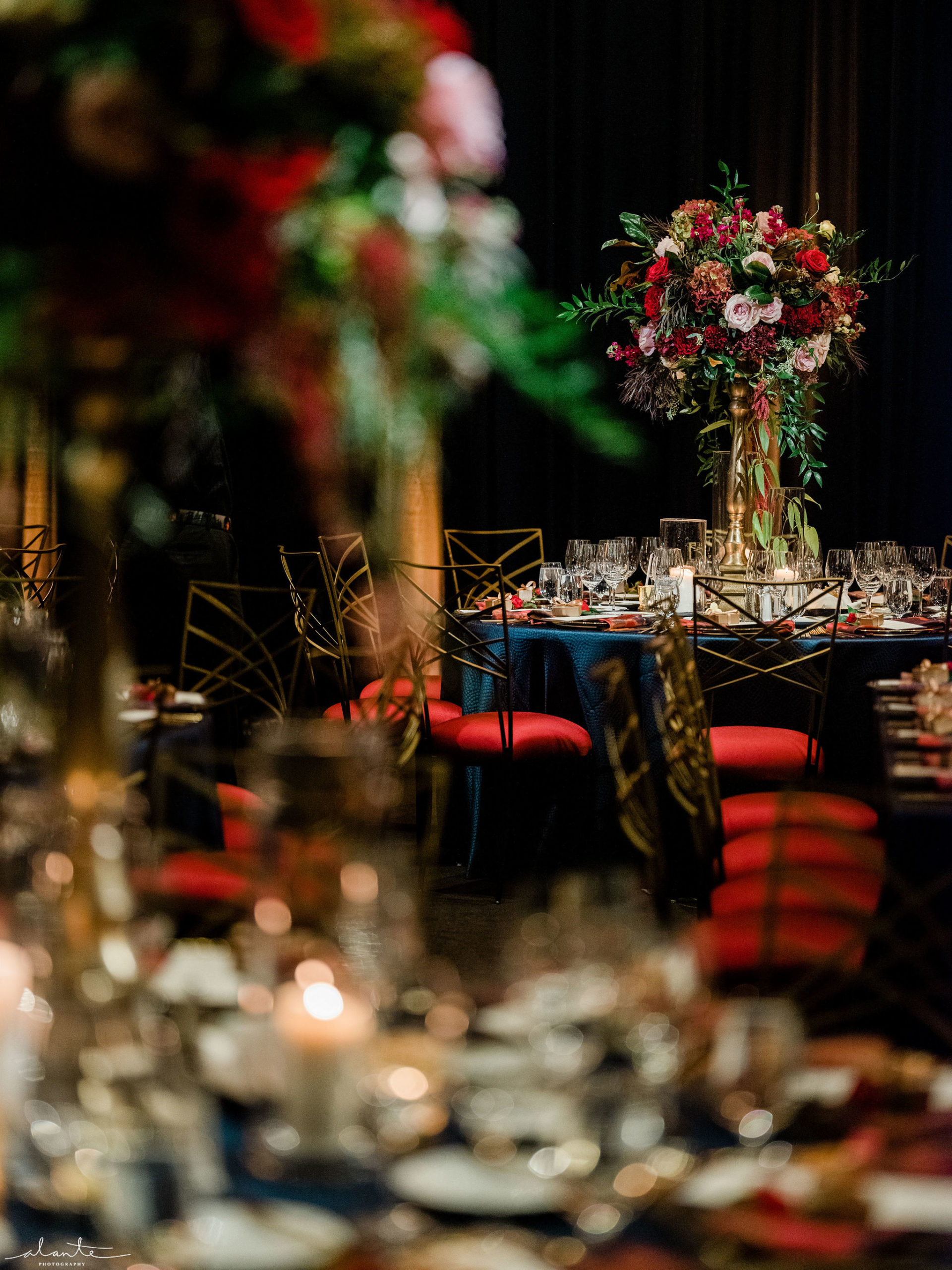 Dramatic winter wedding reception with tall floral centerpieces of red antique hydrangea, roses, and greenery.