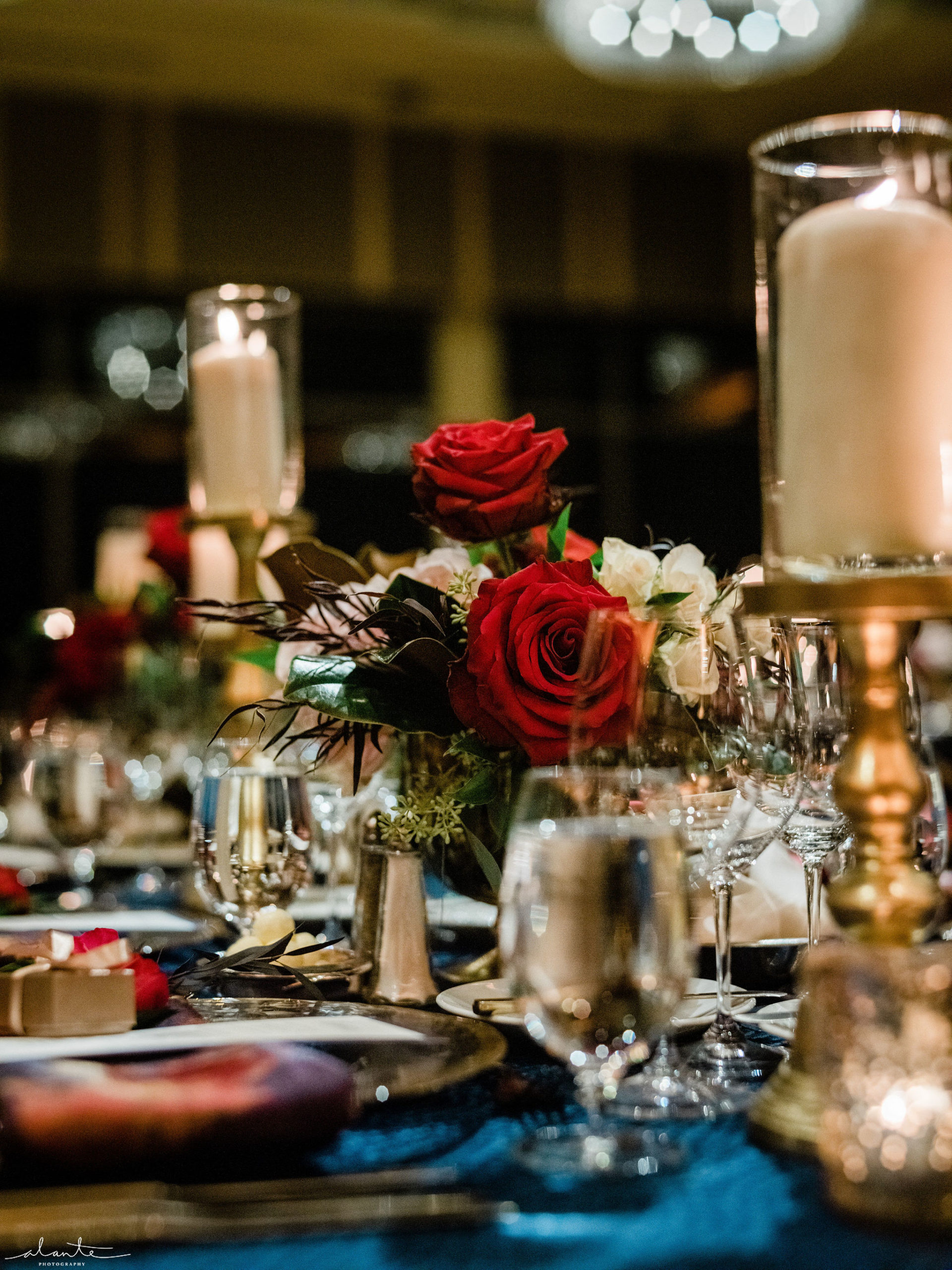 Red winter wedding reception centerpiece of roses and magnolia with pillar candles.