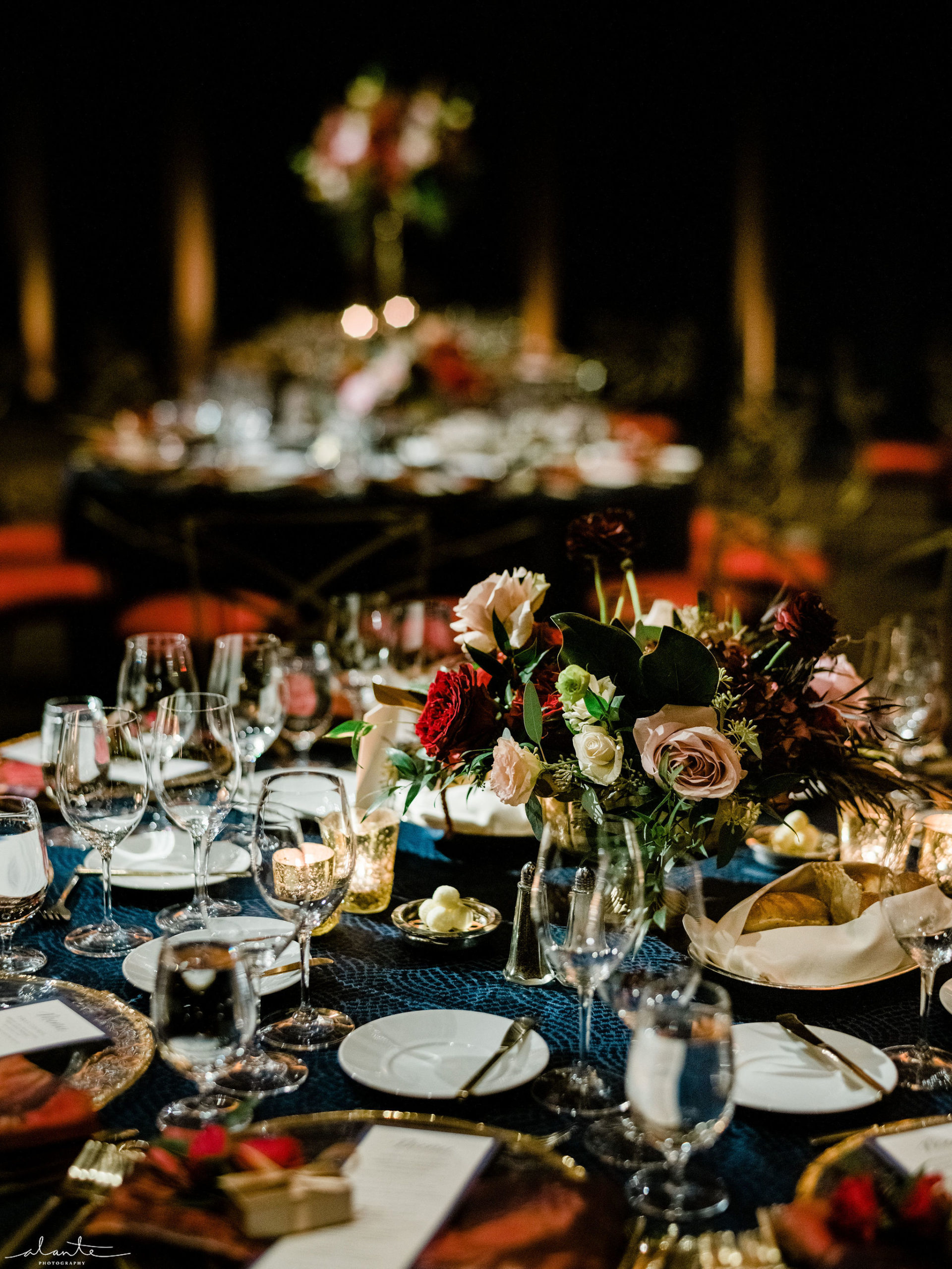 Moody winter wedding reception table setting with navy linens and dark red floral.