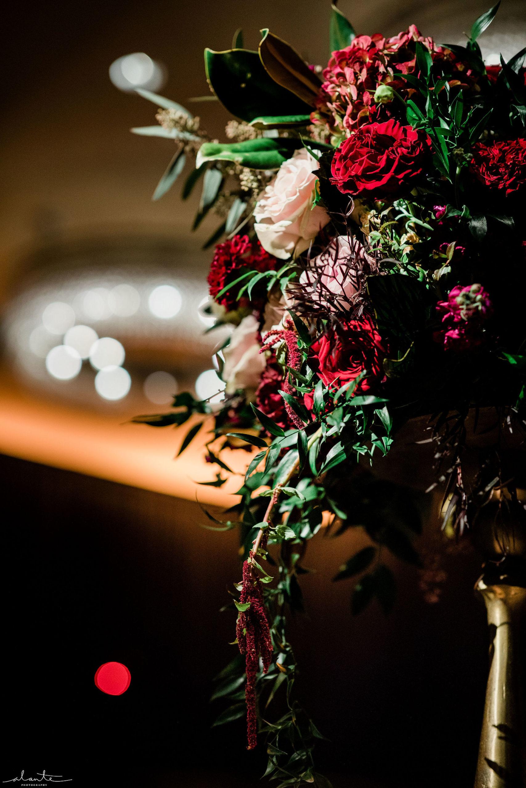 Red roses, antique hydrangea, stock, blush roses and lots of texture and foliages make a memorable winter floral arrangement.