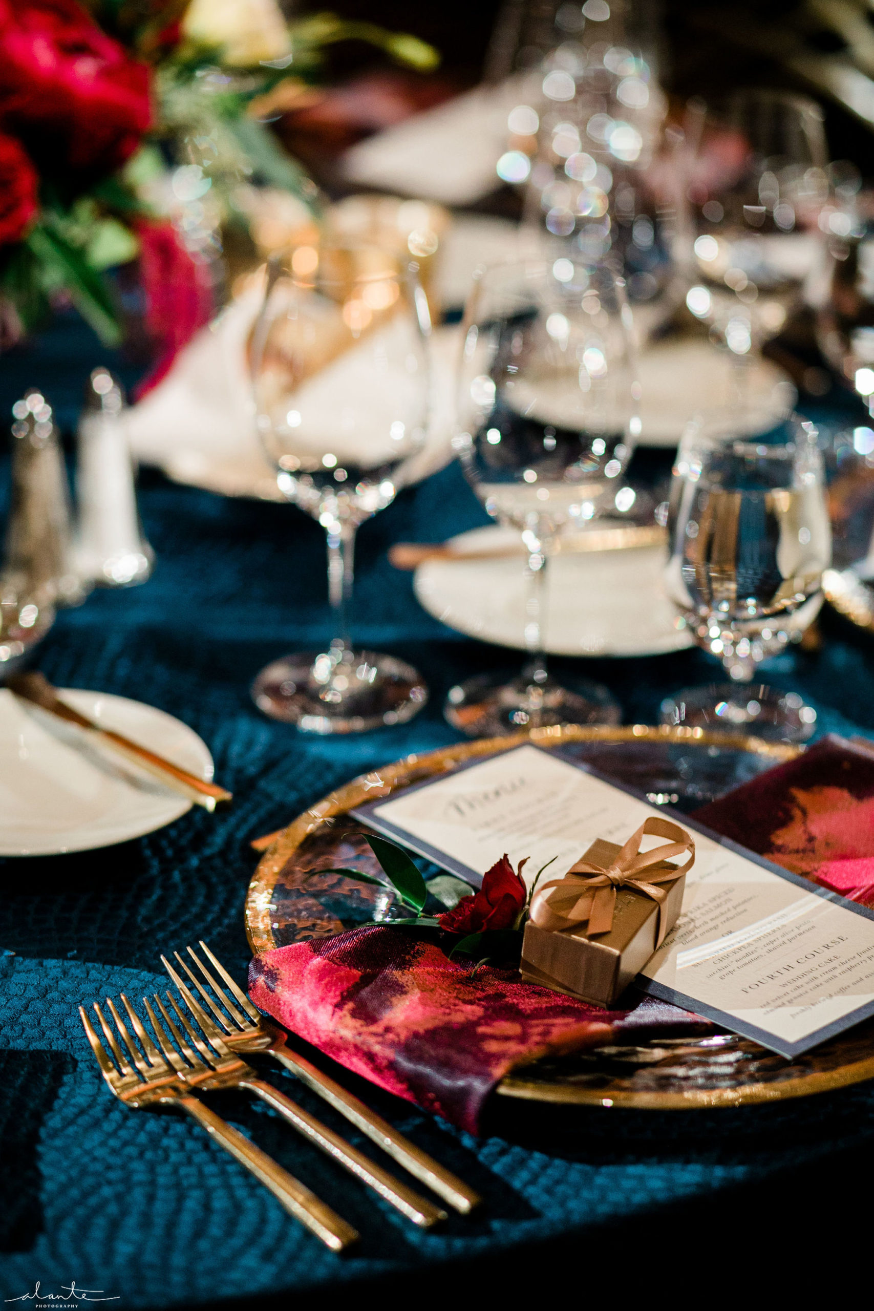 Red winter wedding place setting with red napkins, navy blue linens and gold flatware and charger plates.
