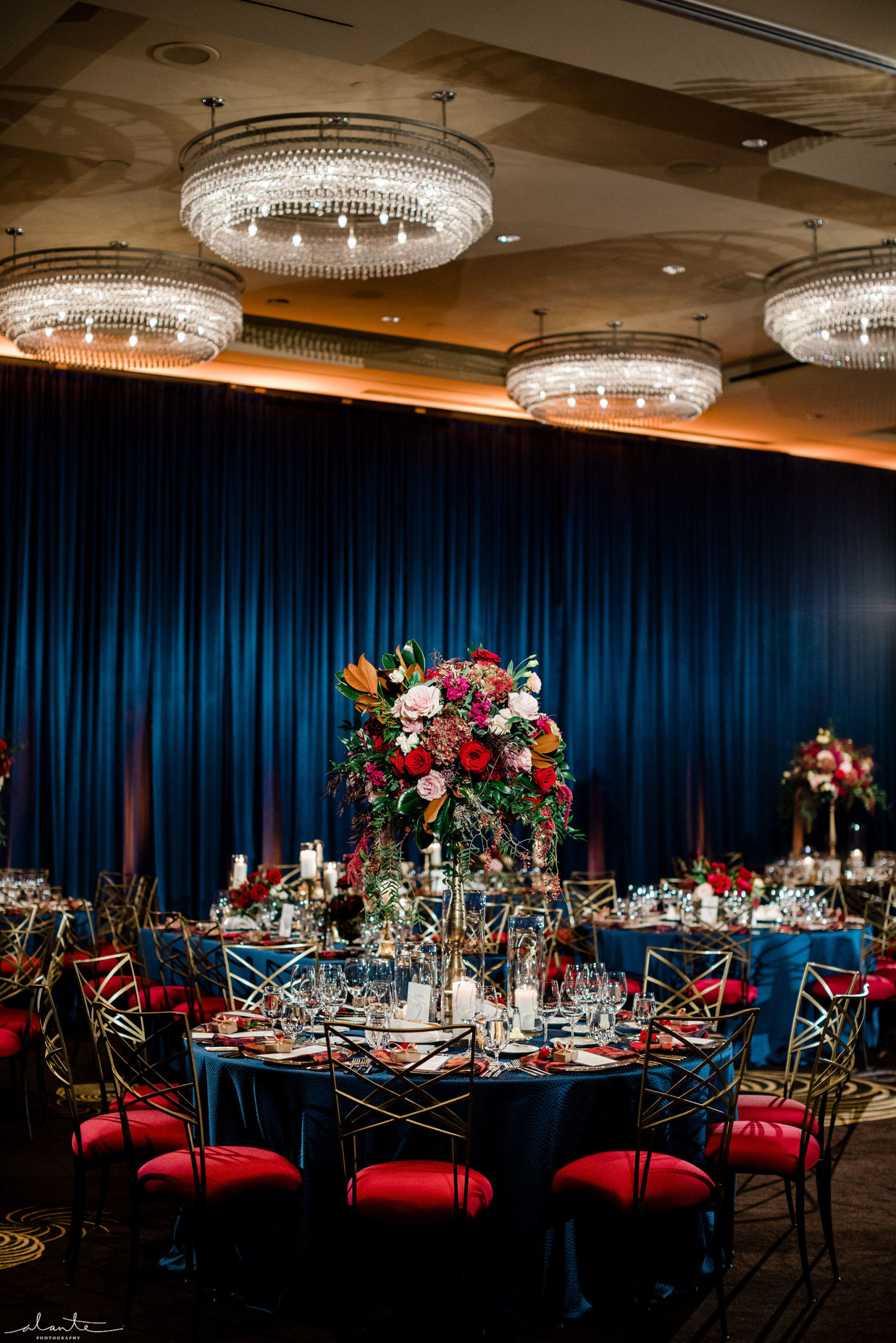 Tall winter floral arrangement for a reception at Four Seasons Seattle with a navy blue draped ballroom.