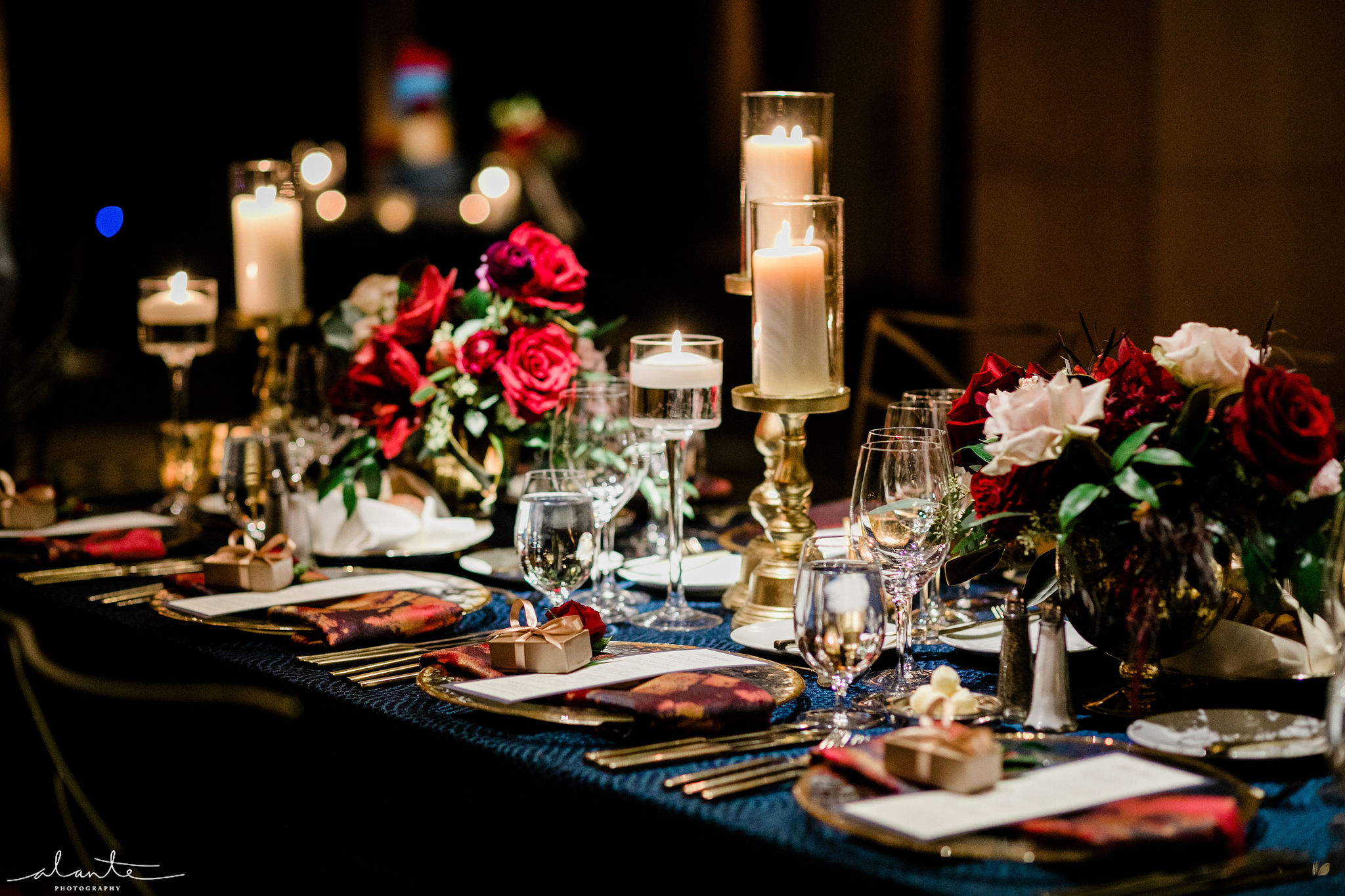 Red and blush roses and eucalyptus low centerpieces along with lots of candles make a cozy winter reception more romantic.