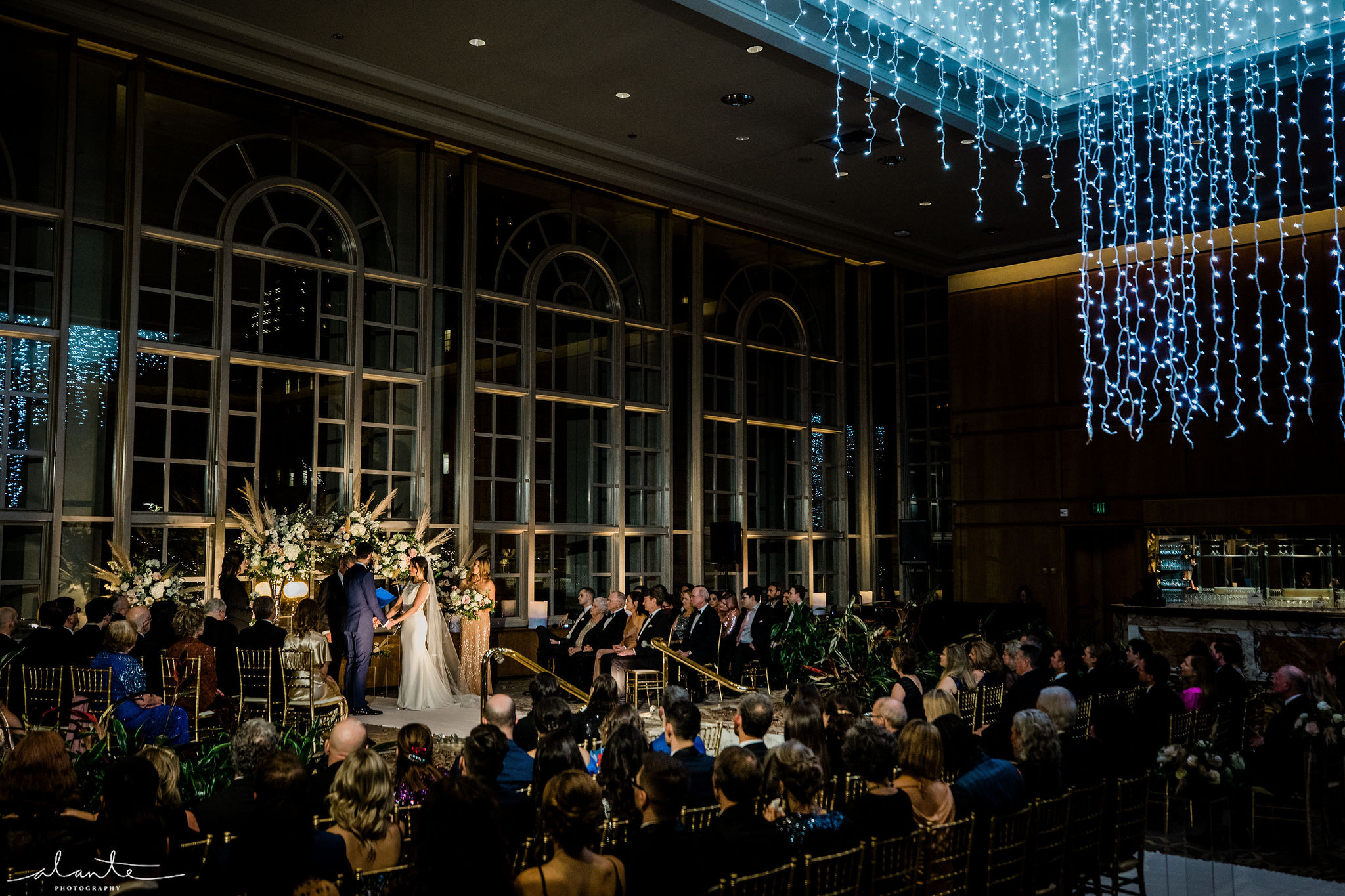 Winter wedding ceremony at the Garden Room at Fairmont Hotel in Seattle, a large hanging holiday light chandelier fills the room with a romantic glow.