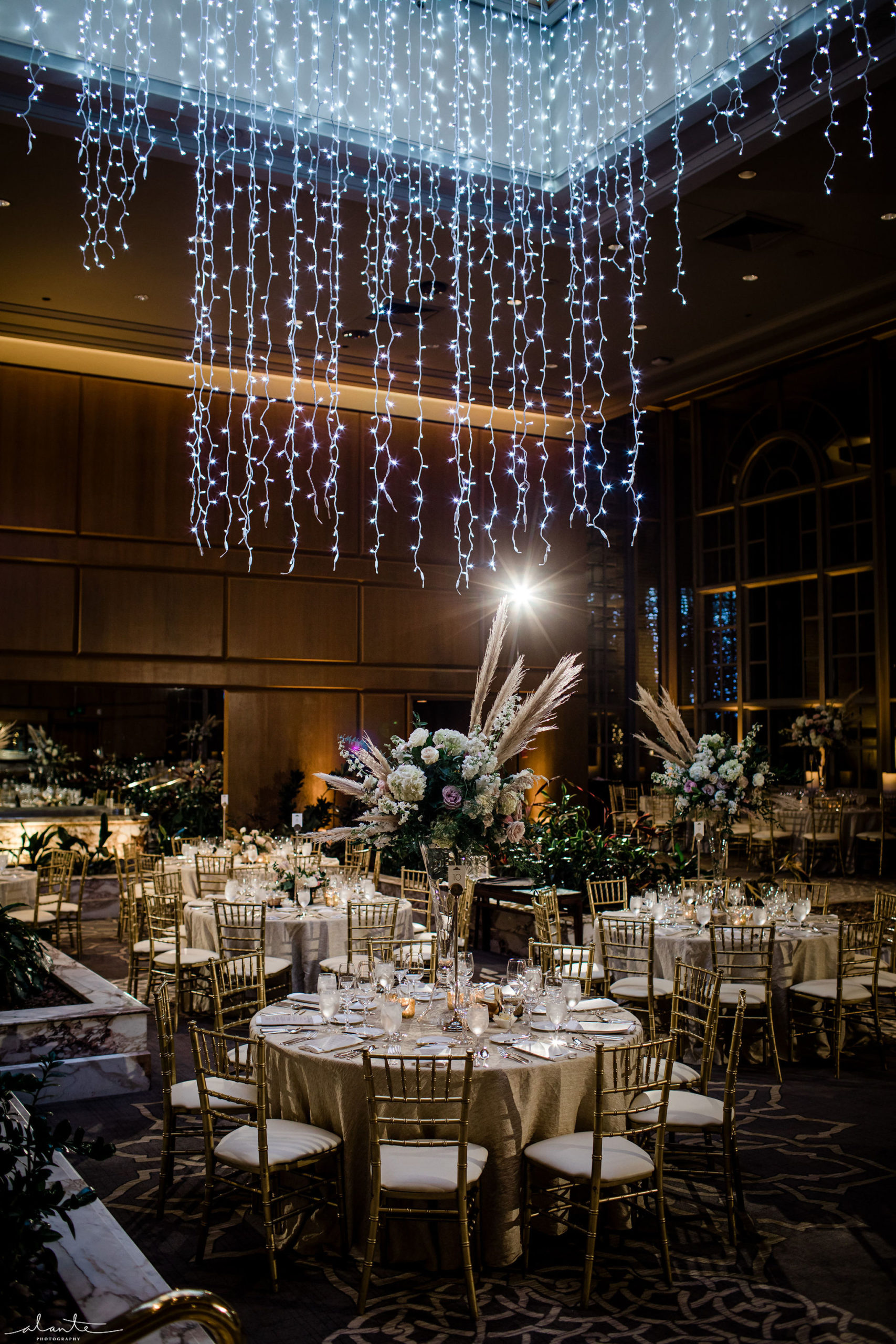 New Years Eve wedding reception with gold tables and chairs and tall white floral under a hanging Christmas light chandelier.
