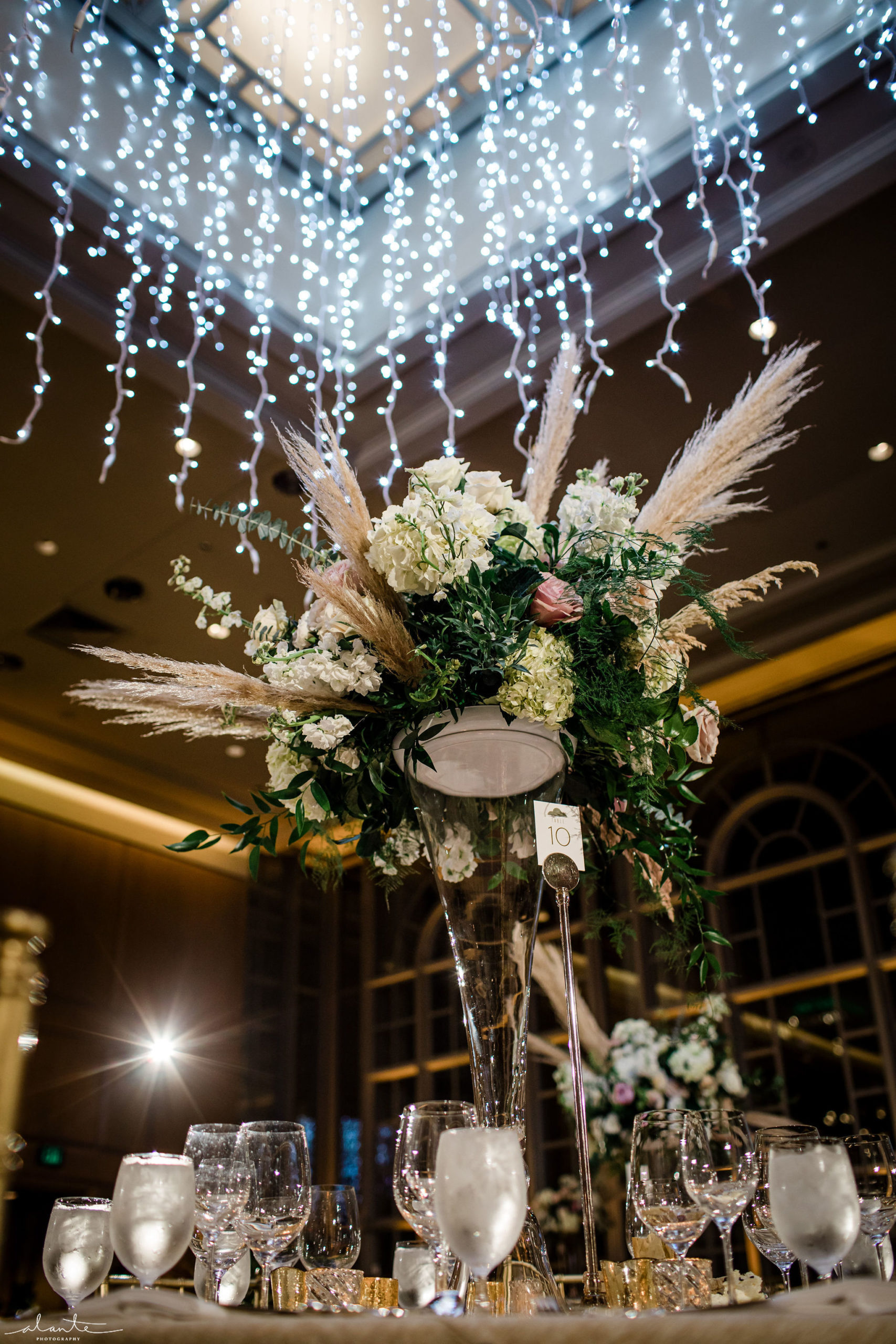 Tall floral centerpiece with hydrangea, roses and pampas grass under a holiday light chandelier hanging from the ceiling.