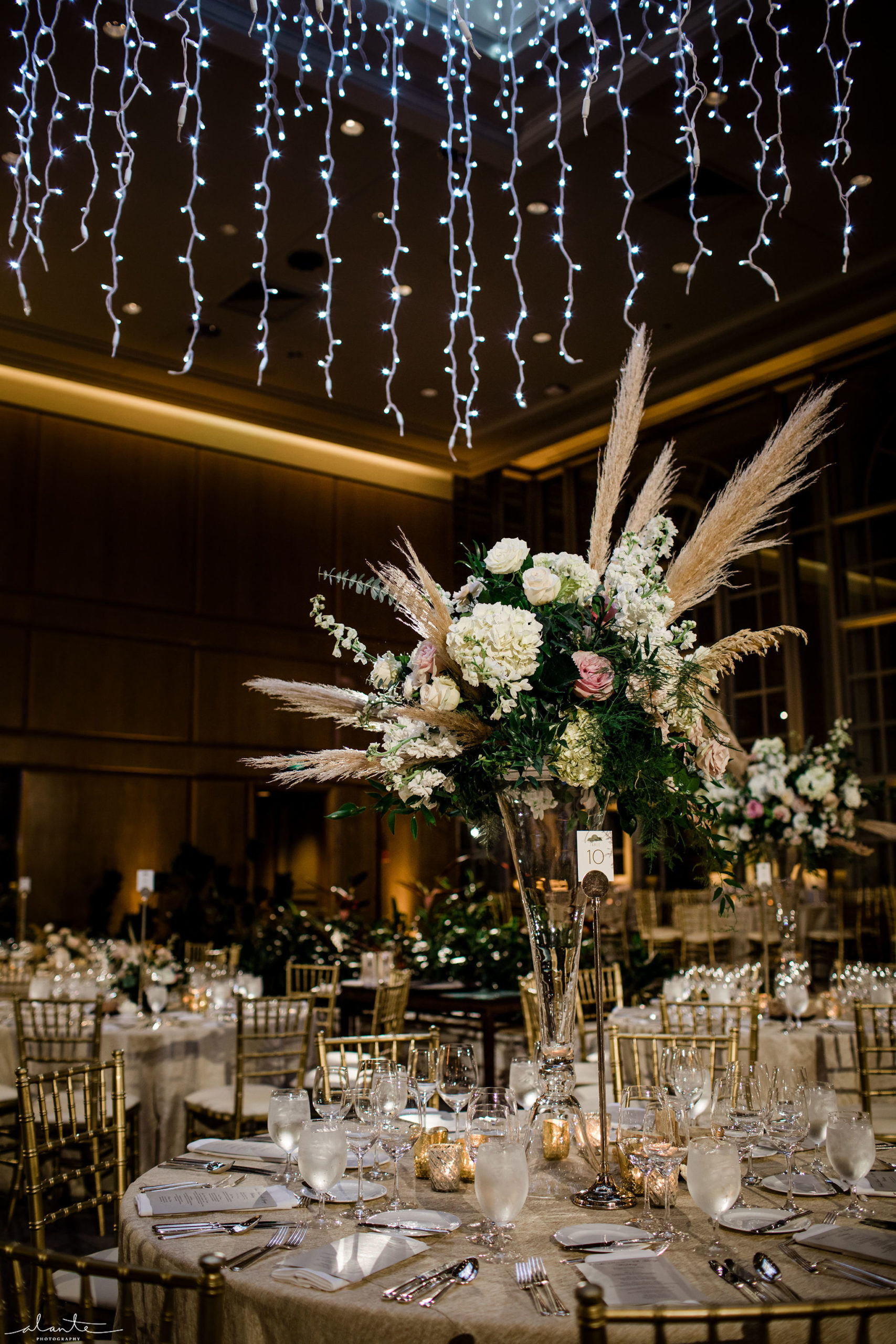 Pampas grass wedding winter reception with tall centerpieces of white and mauve floral with pampas grass.