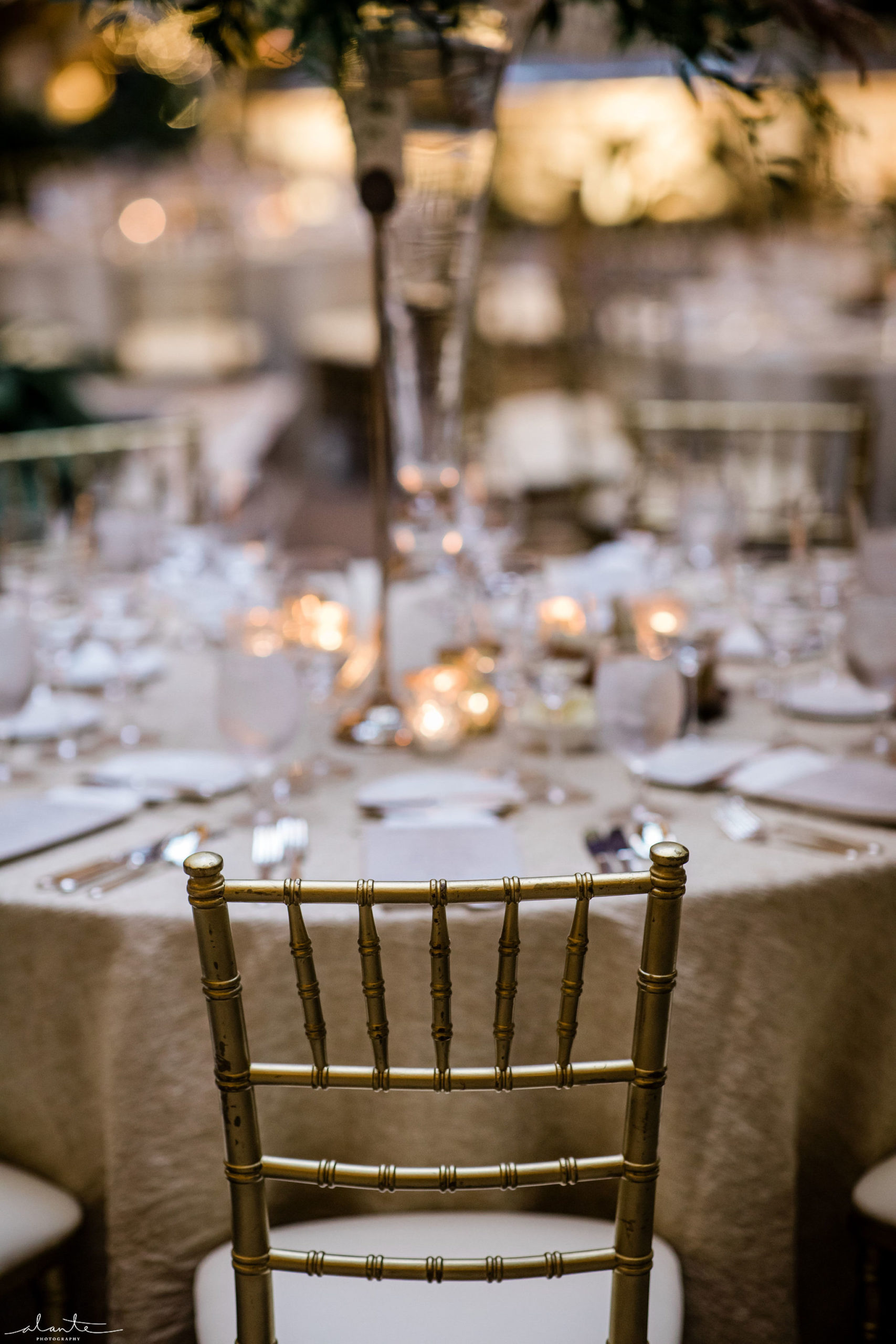 Gold charivari chairs at a round reception table with gold linens and a tall floral arrangement.