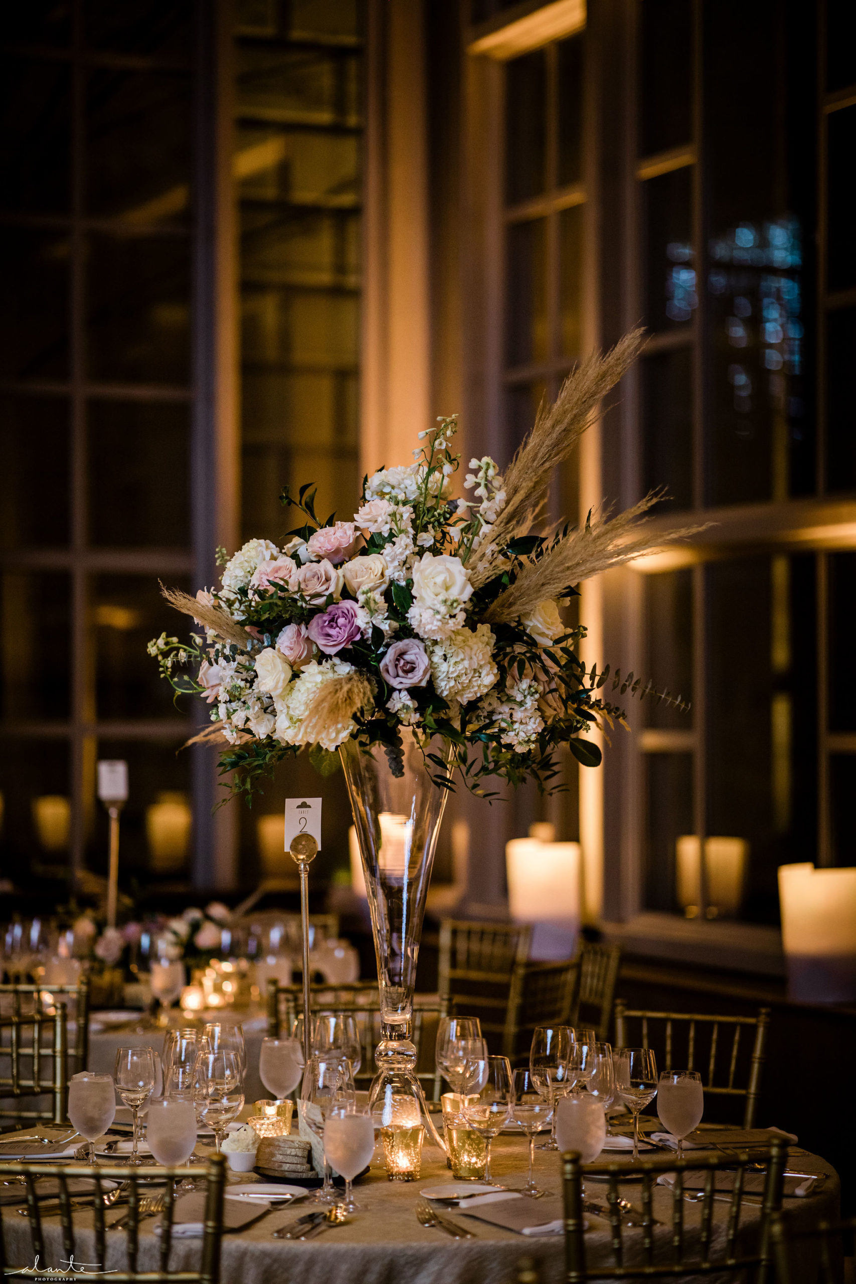 Tall floral centerpieces in white and mauve with pampas grass in a candlelit ballroom with soft uplighting.