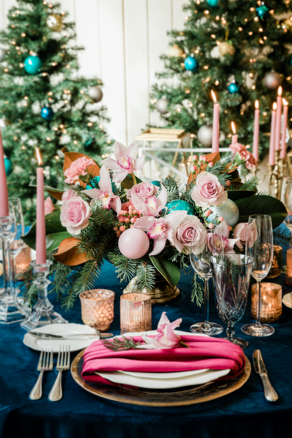Pink and turquoise centerpiece for the holidays, with pinkn roses, and pink orchids, turquoise ornaments, red velvet napkin, navy linen and Christmas trees