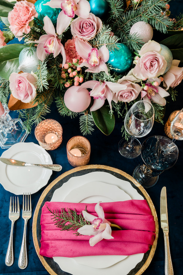 Decorating for the Holidays: Pink and turquoise centerpiece for the holidays, with pink roses, and pink orchids, turquoise ornaments, red velvet napkin, navy linen and Christmas trees