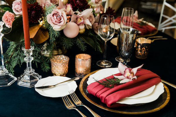 Holiday dinner table with navy linen, red velvet napkin, gold votive candles, pink roses and pink ornaments