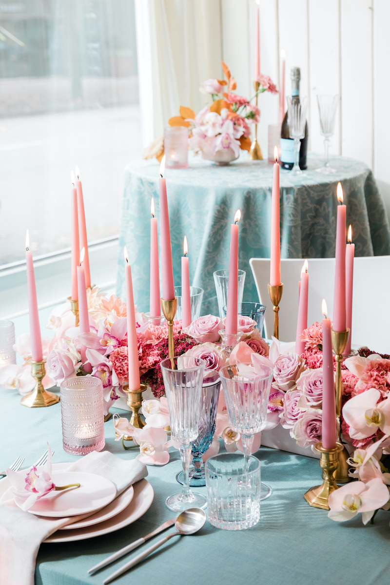 Pink lush low floral centerpiece with taper candles set for a intimate dinner date.