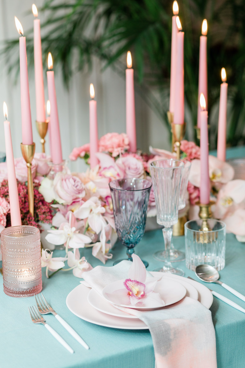 Lots of tall pink taper candles are nestled into a monochromatic low pink floral centerpiece running down the length of the table.
