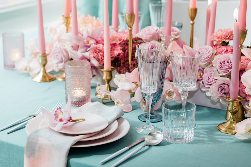 Mauve flowers, baby pink, blush, into the deep pinks all create depth and interest in this all pink floral centerpiece paired with bright teal linens.