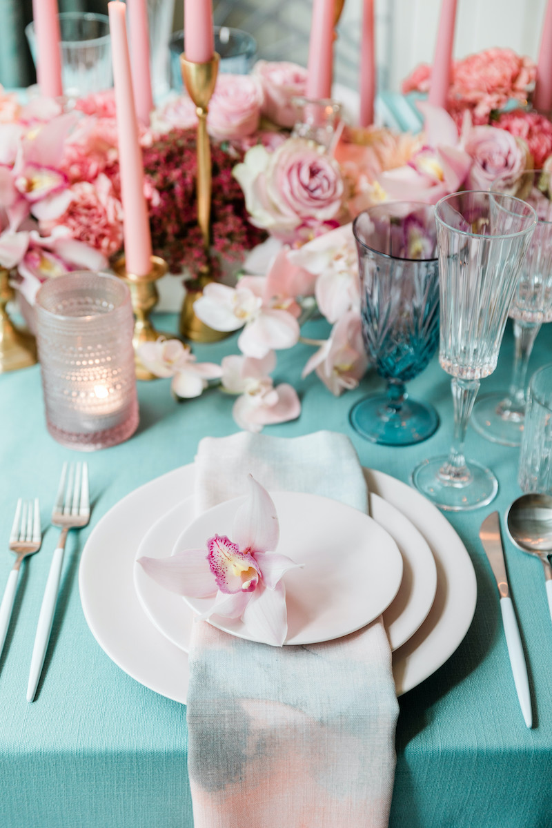 A pink cymbidium orchid on every place setting with pink floral low centerpiece with a fresh pop of teal linens and glasses.