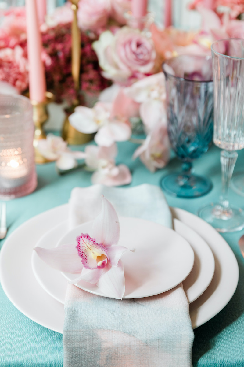 A pink cymbidium orchid on a light pink stoneware place setting with pink floral low centerpiece with a fresh pop of teal linens and glasses.