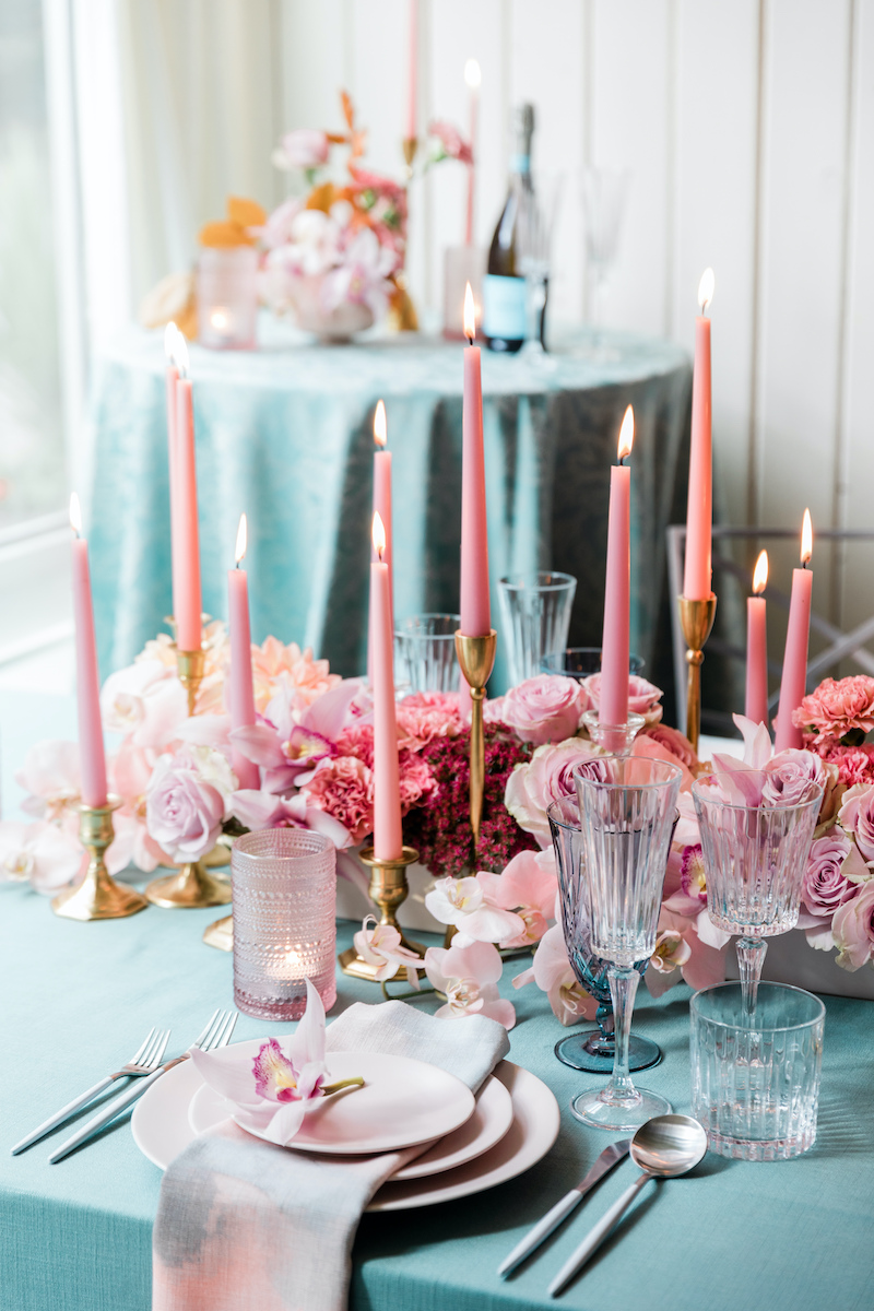 Teal and pink dinner party table setting, with pink floral, candles, and plates and teal linens.