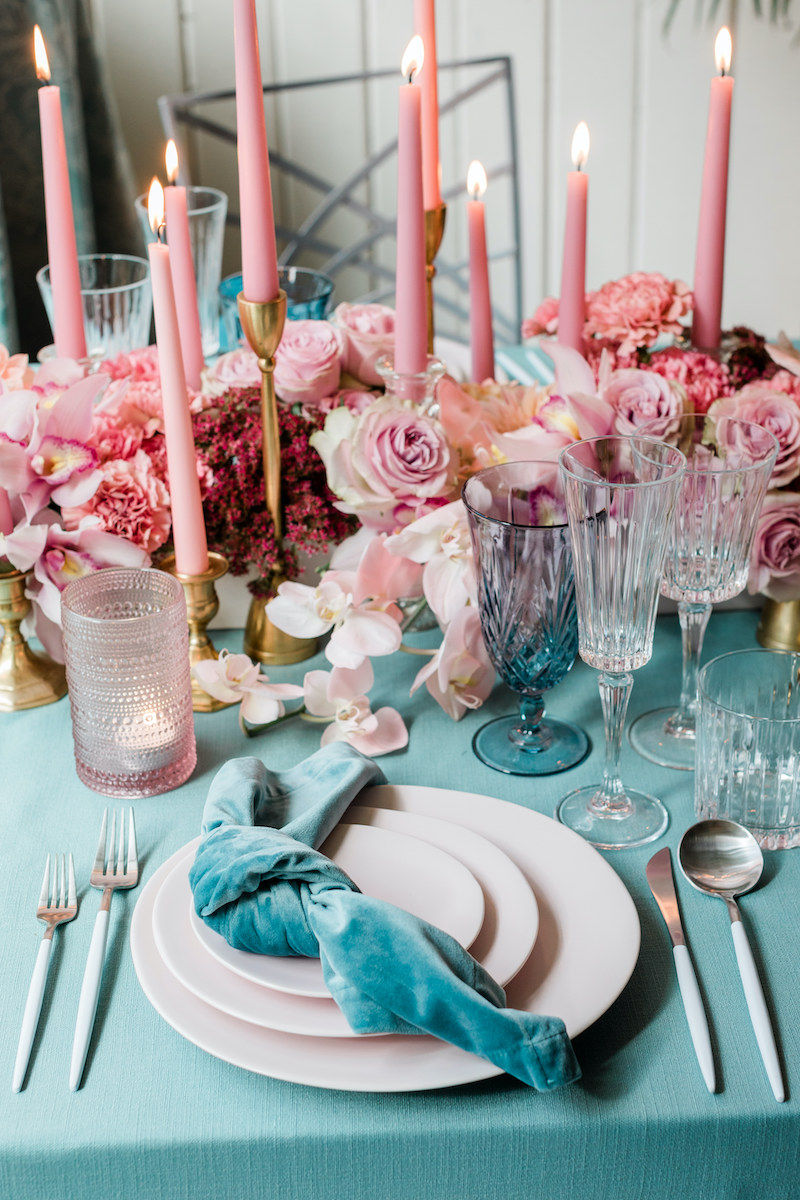 Low lush pink floral centerpiece of roses, orchids, and carnations and pink taper candles line the center of the long dining table on a teal linen.