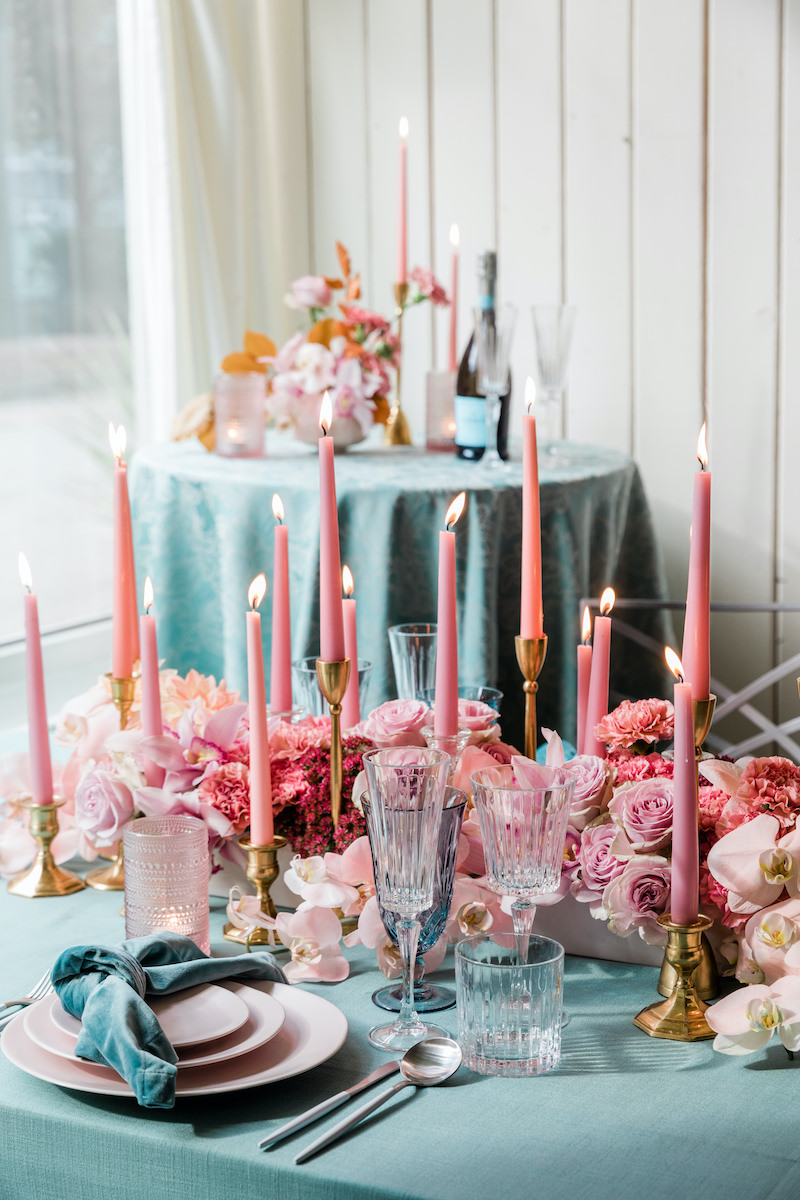 Teal velvet napkins on light pink plates with pink flowers and taper candles for a romantic Valentines dinner date table setting.