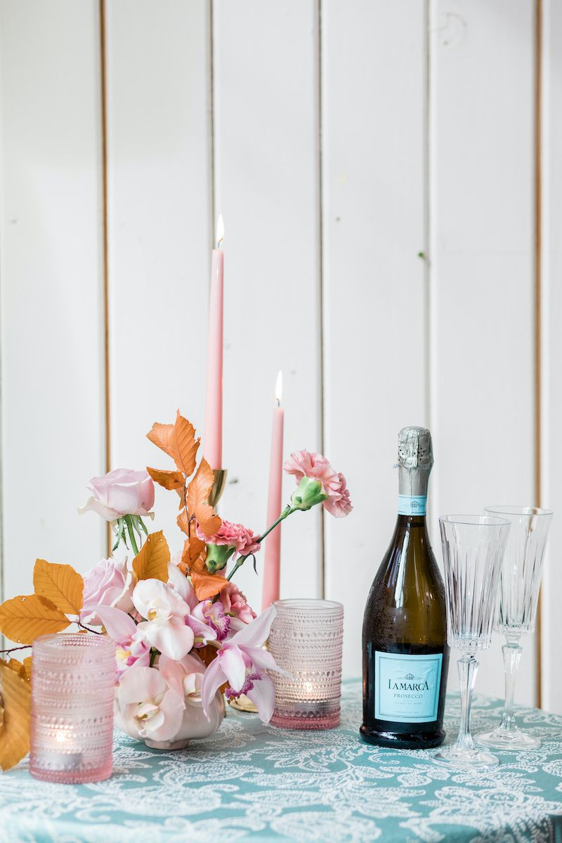 Light pink floral arrangement paired with pink candles on a side table in turquoise linen set for a champagne toast.