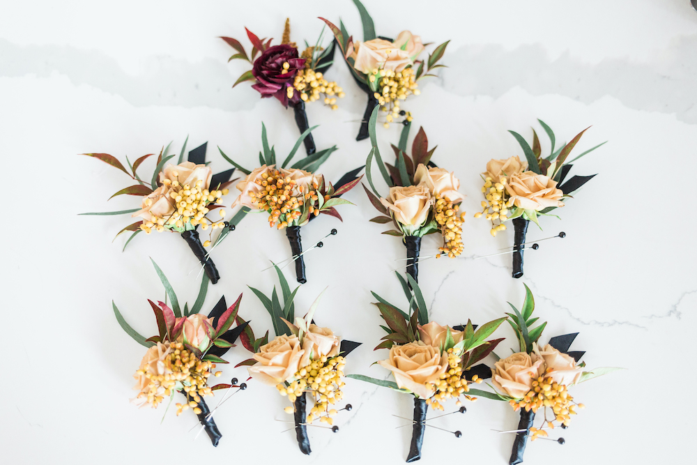 Fall colored boutonnieres for wedding with orange roses and fall foliage