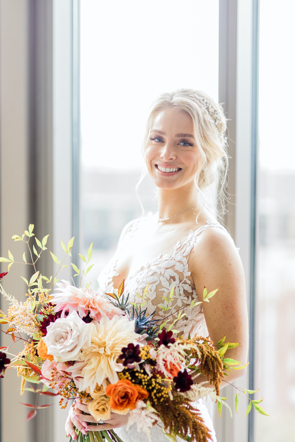 Bride holding her fall floral bouquet with Cafe au Lait dahlias, orange roses, chocolate cosmos, and fall foliage
