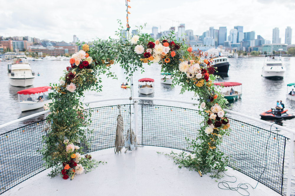 Wedding arch with greenery and fall flowers on ferry in Lake Union in Seattle with guests following in own boats - a Safe Pandemic Wedding Seattle