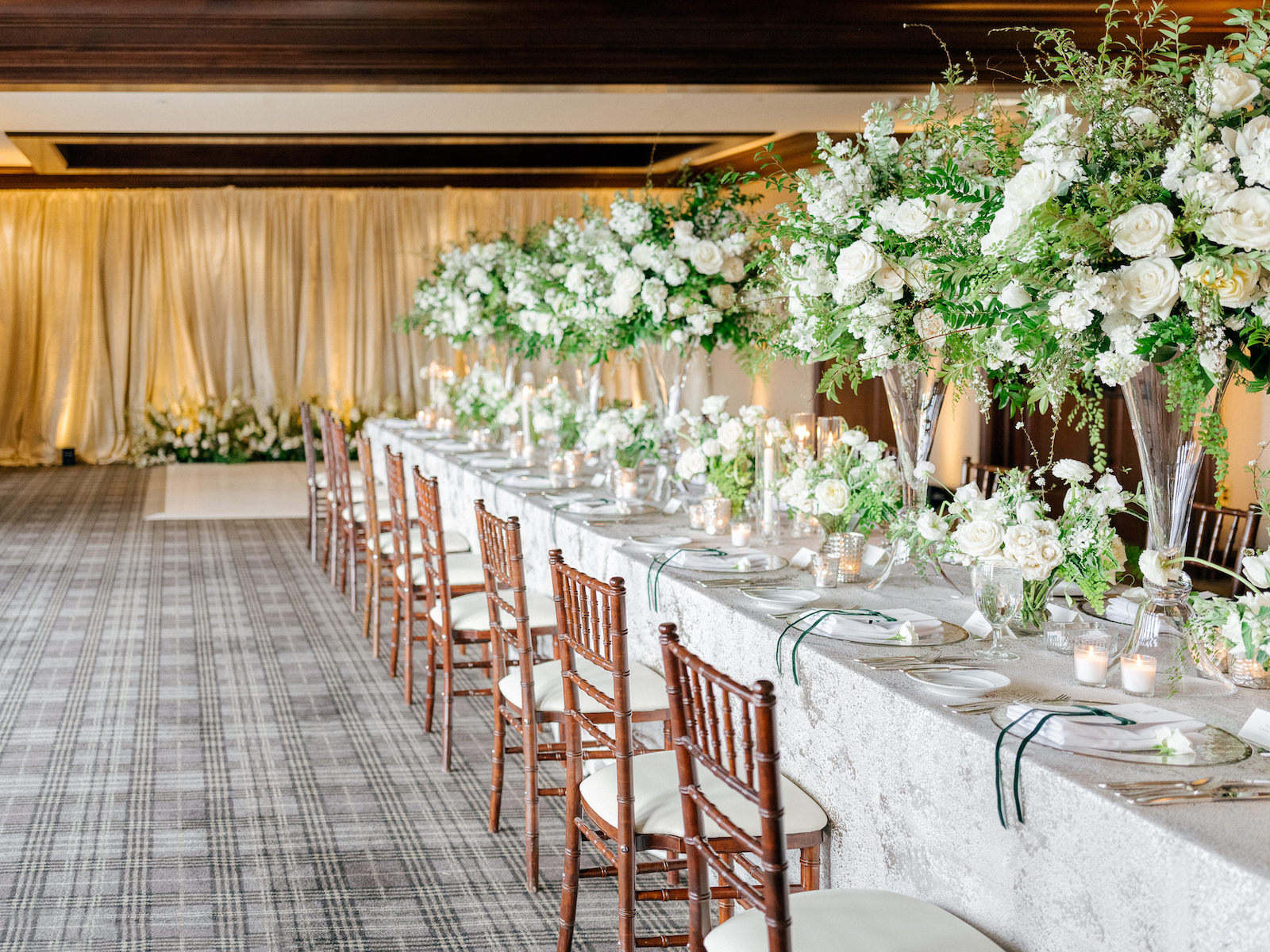 A long wedding reception table lined with tall and low floral centerpieces in glass vases, with brown Chivari chairs for Spring Wedding in White and Green