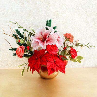Centro de mesa navideño con flores de pascua, amarilis, rosas de jardín y acebo