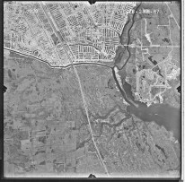 """This 1970 photo shows three of the features that would become emblematic of contemporary Florida: the decentralized suburban sprawl of Port St. Lucie at the top of the image, the canalization of a small natural river into the flood control and irrigation C-24 canal, and a prominent golf course (on the right side of the image) (University of Florida, """"Aerial Photographs of St. Lucie County—Flight 2MM [1970],"""" Map and Imagery Library, Gainesville)."""