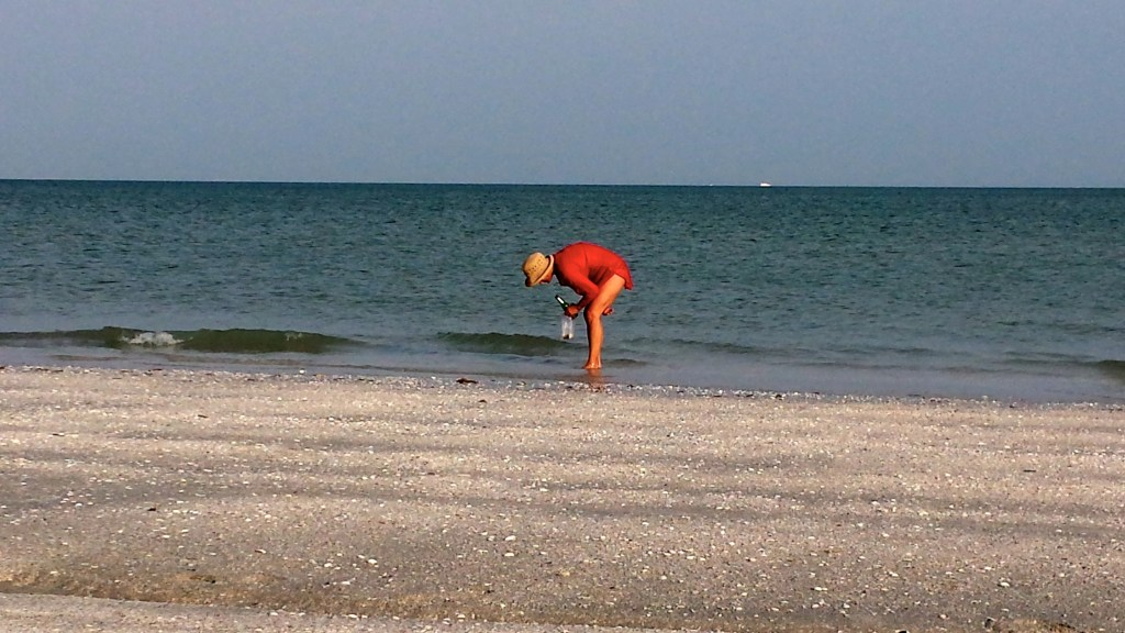 A lady doing the Sanibel Island Stoop at water's edge!