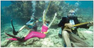 Participants pretend to play mock musical instruments during the Lower Keys Underwater Music Florida Keys Reefs