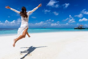 Woman jumping in white dress