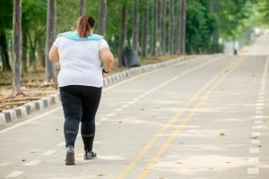 Rear view of overweight woman wearing sportswear while jogging on the road