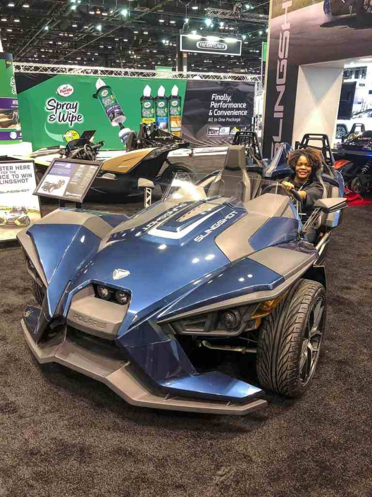 Blue Polaris Slingshot with woman sitting in drivers seat