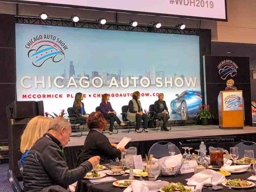 Four women sitting on a stage discussing women's integral role in the automotive industry while an audience with mostly women look on