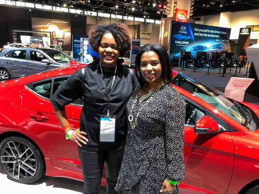 2 African American women smiling at the camera.  They are standing in front of a red car.