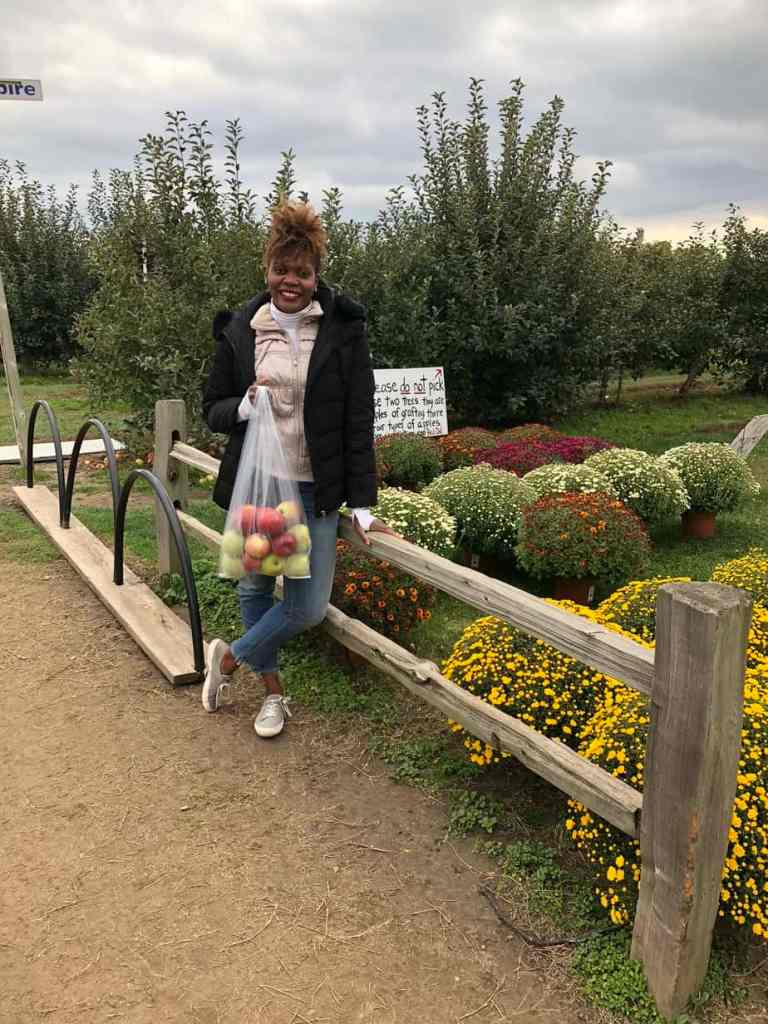 Woman smiling holding a bag of apples at Crane U-Pick Orchards