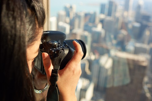 Woman capturing a picture of the Chicago Skyline from the top of the John Hancock Building