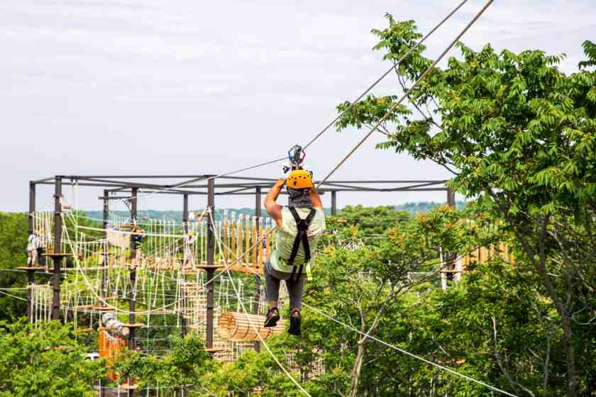Man zip-lining over trees at The Forge Lemont Quarries