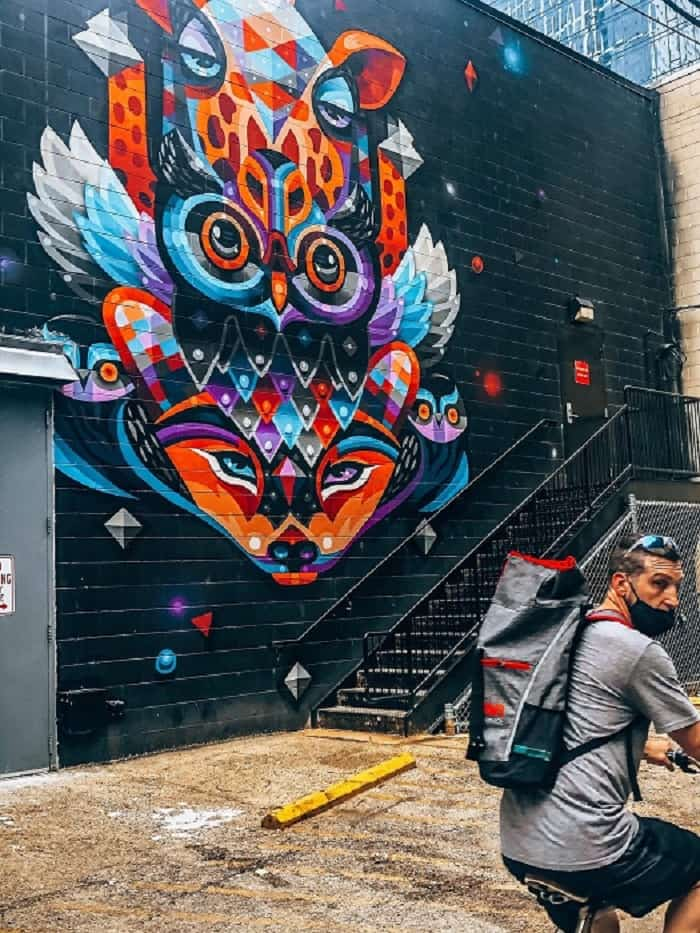 Man riding bike by a colorful mural