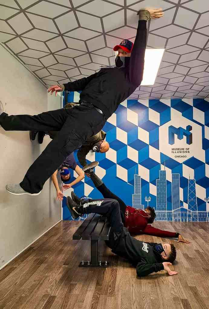 5 people seemingly defying gravity at the Museum of Illusions Chicago